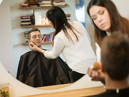 A man in a salon cape being treated by a woman.