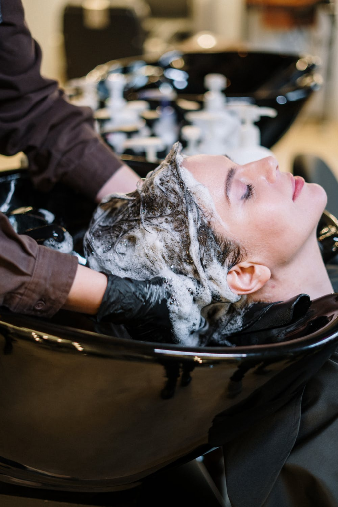 A professional hair dresser her pampering a client at a hair salon.