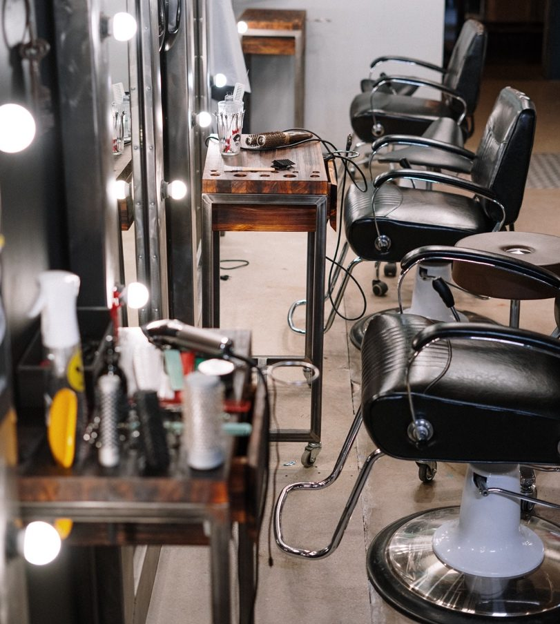 A well-lit beauty salon with leather chairs